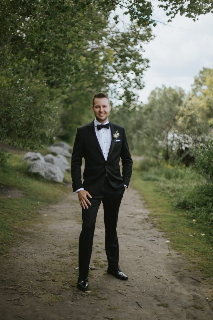 groom stands on path wearing a suit