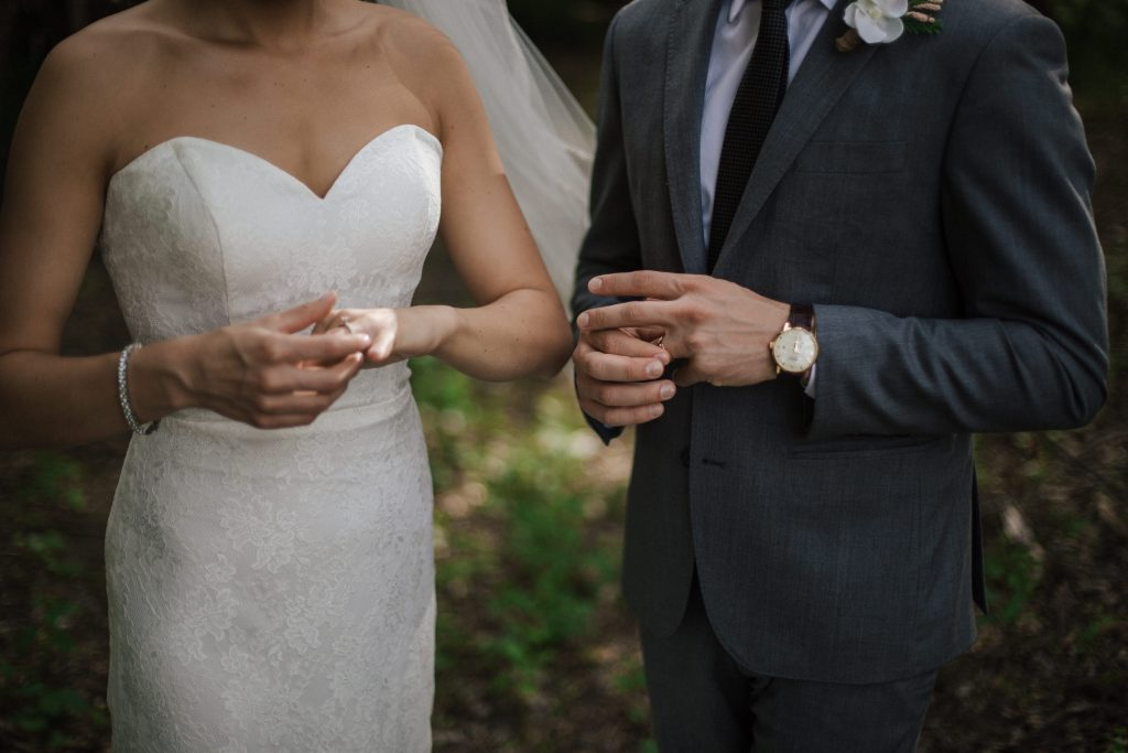 bride and groom play with their rings