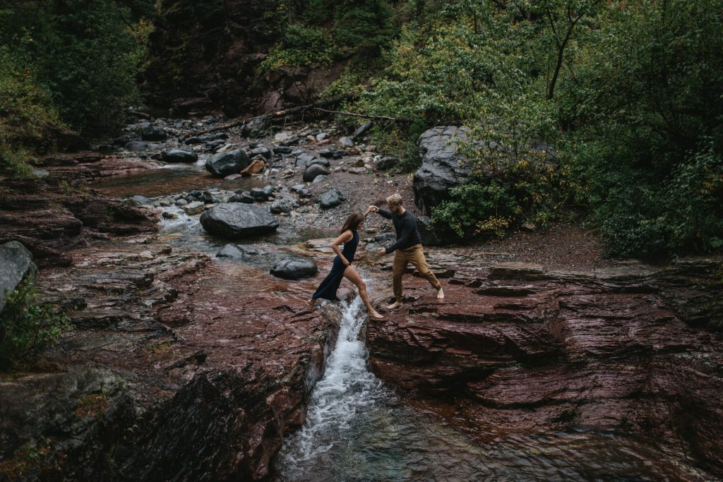 couple jumps across a creek onto red rocks