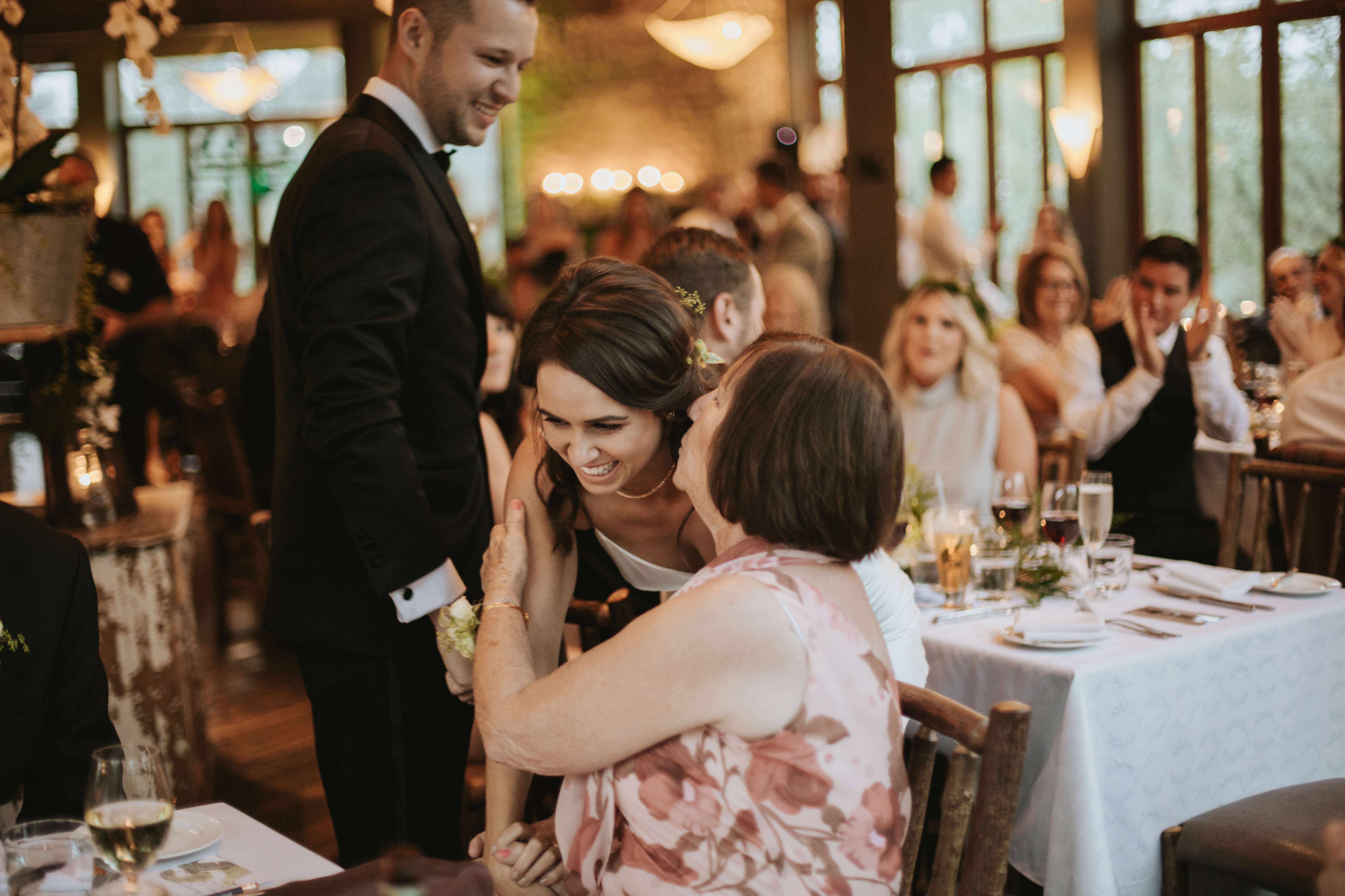 the bride enters the reception and is kisses by an aunt