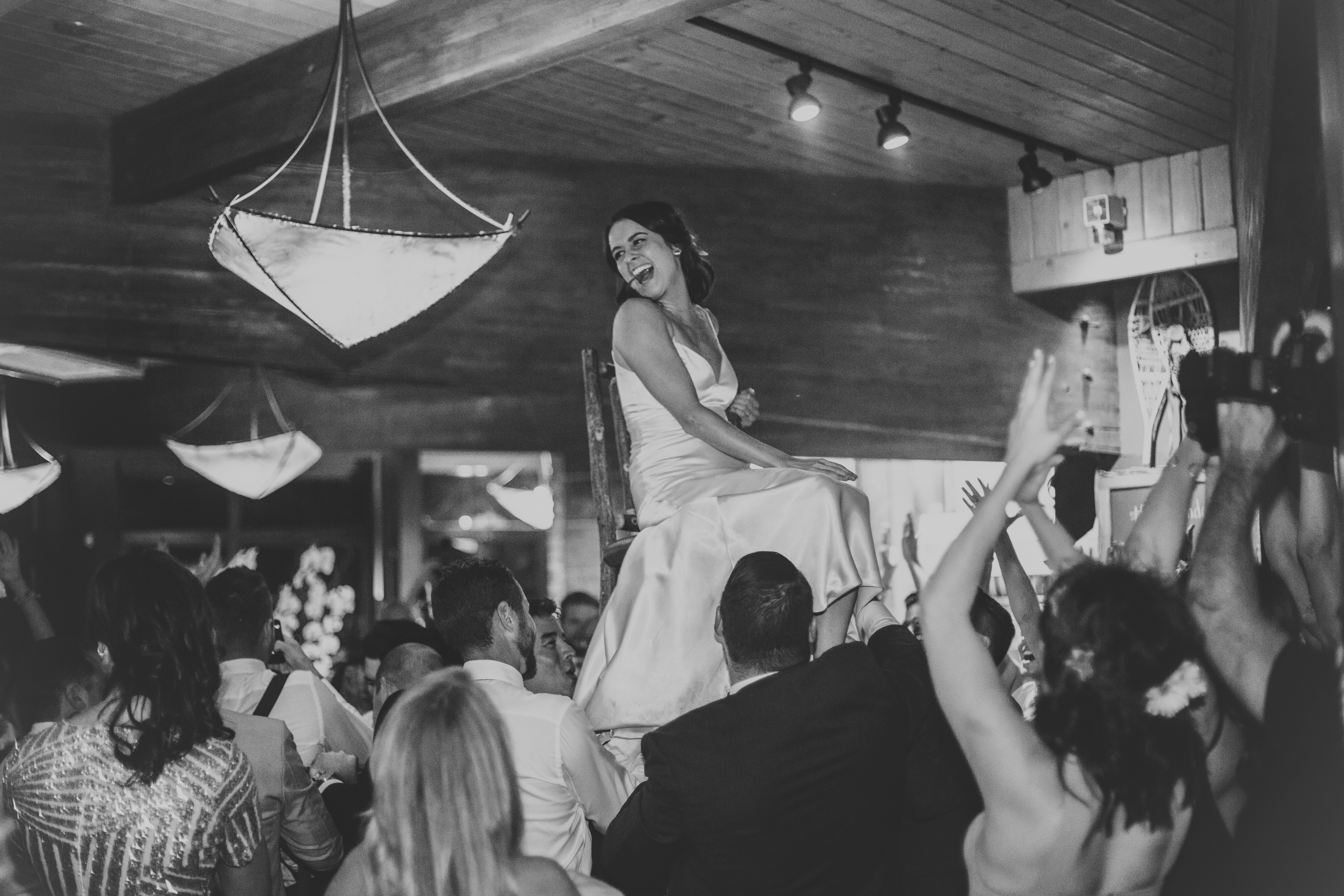 bride high on a chair during the hora