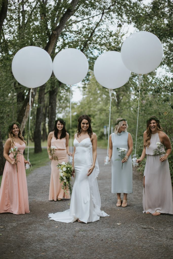 bridesmaids holding balloons and laughing