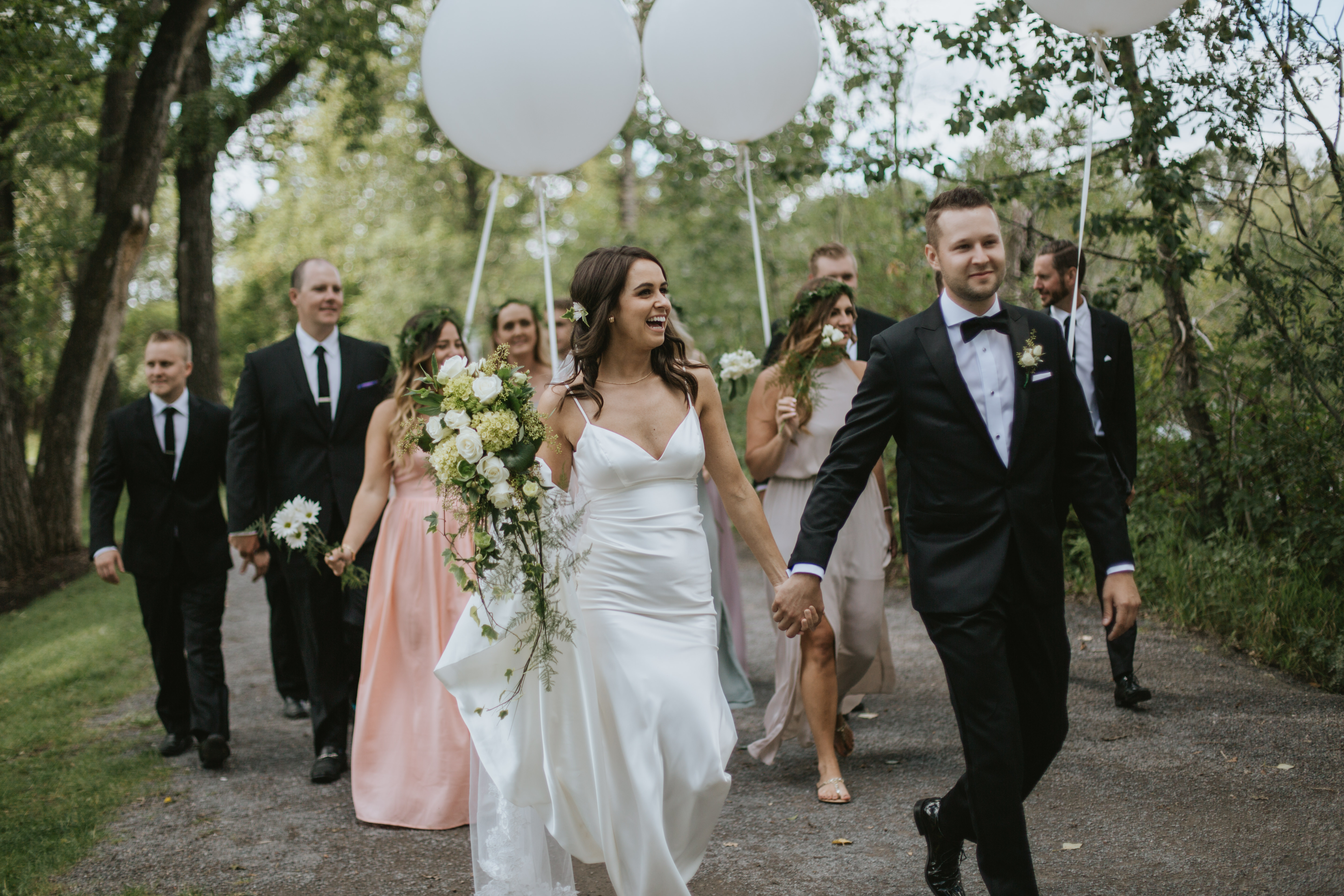 bridal party walking and laughing with balloons