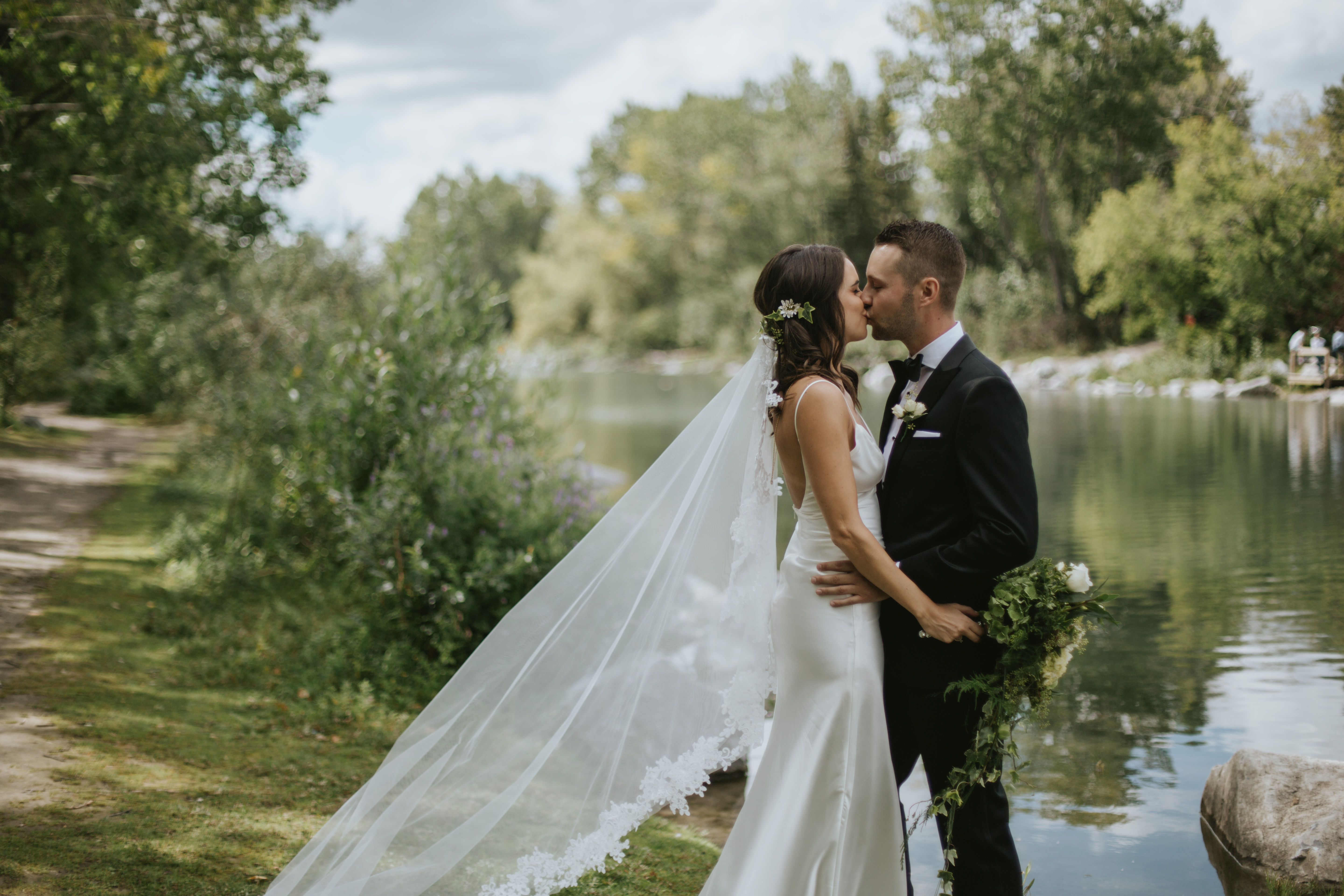 bride and groom kiss by the bow river