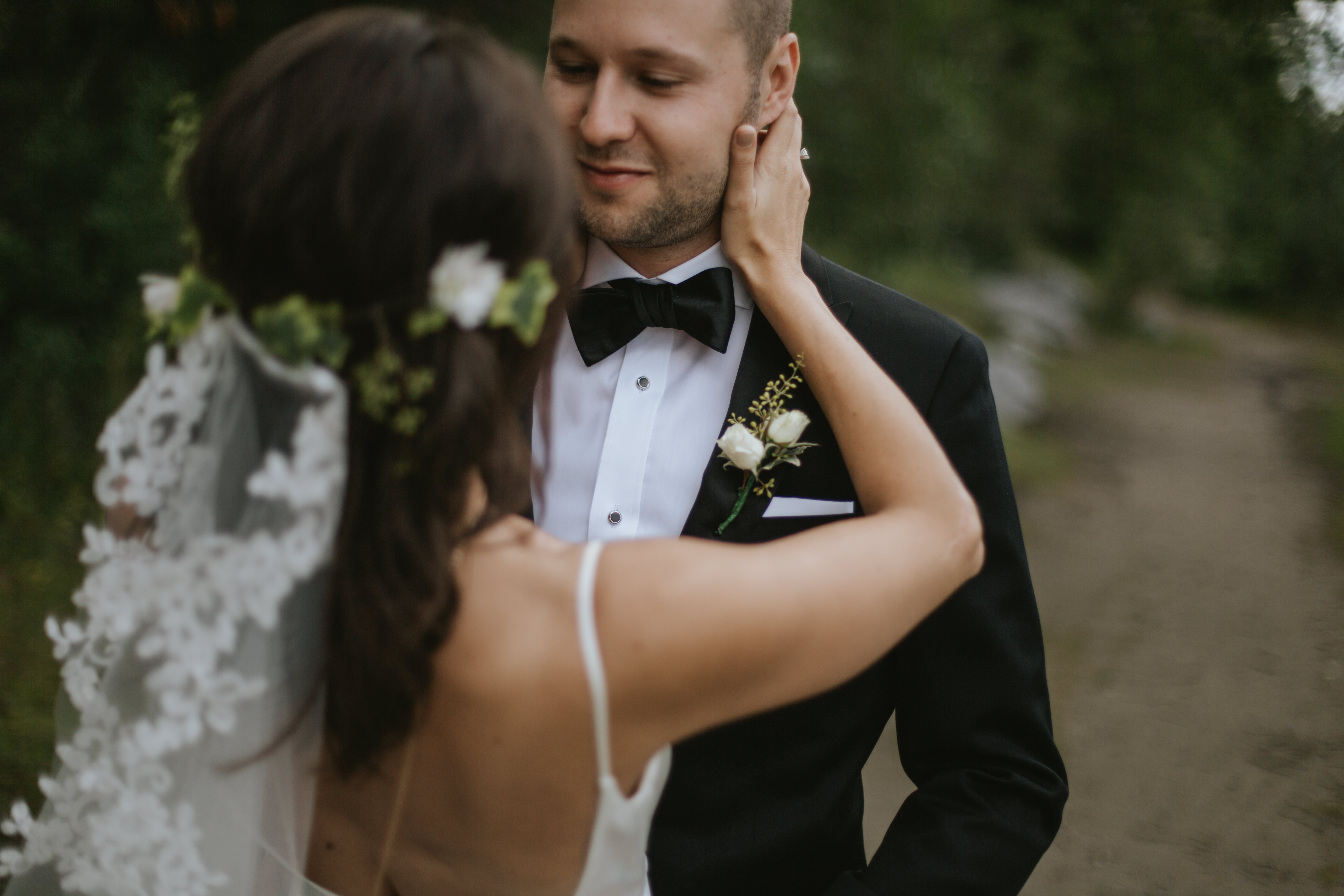 bride touches grooms face in princes island park