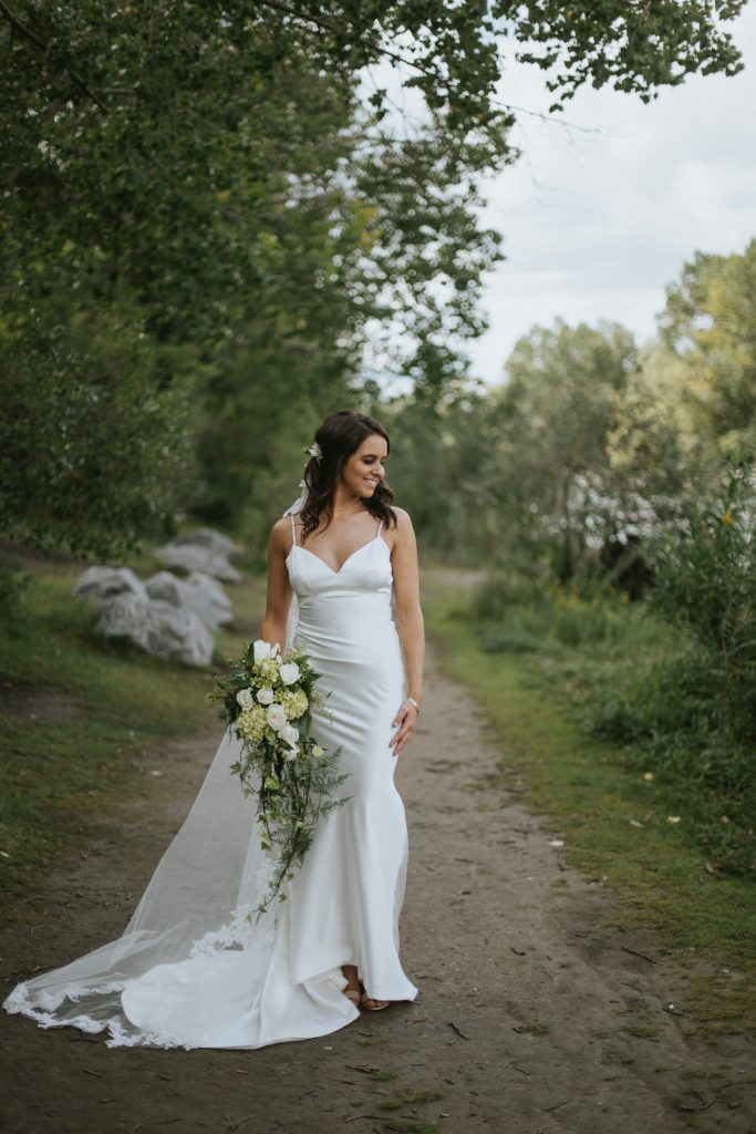 brides holds bouquet and looks out at the river