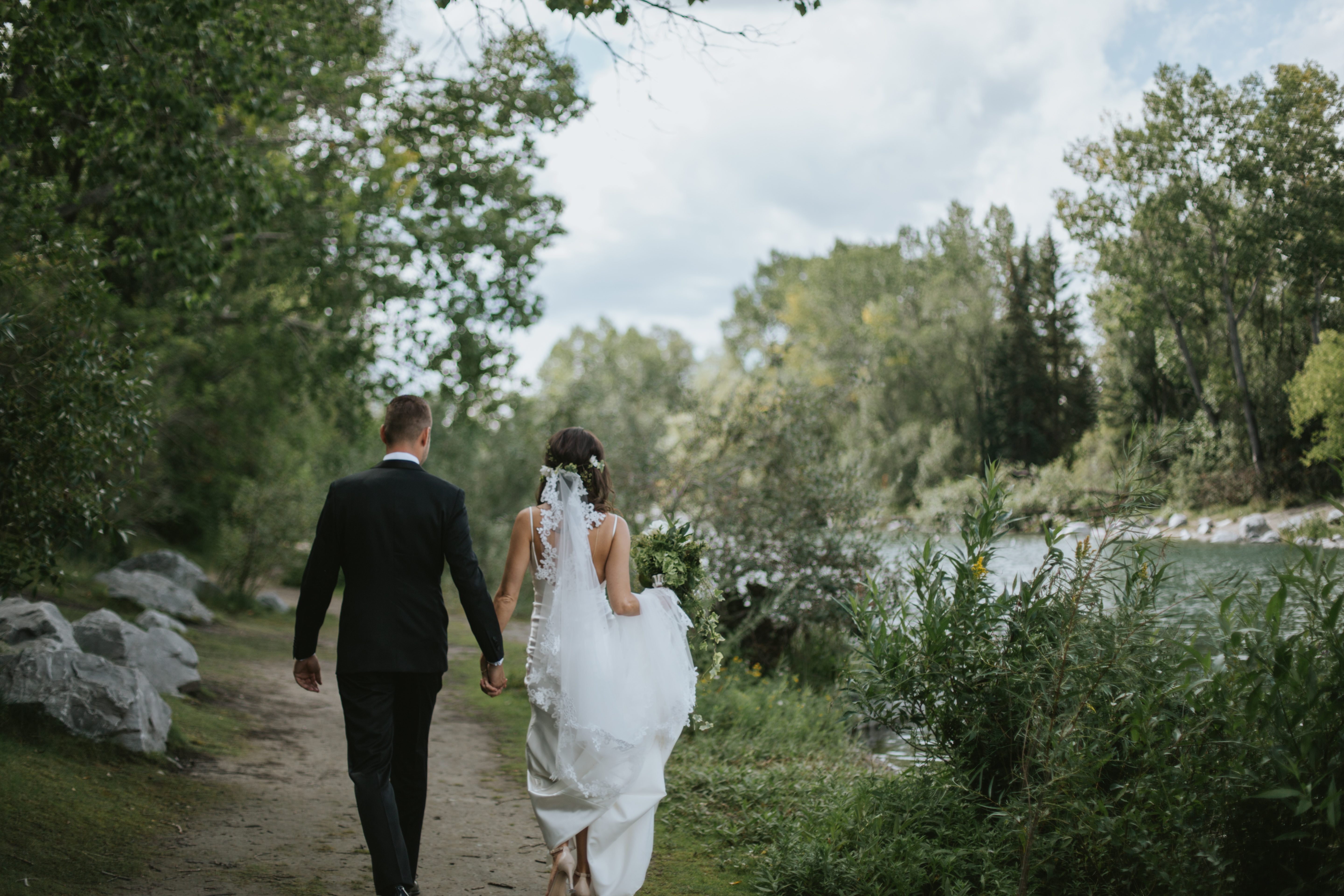 bride and groom walk along the river path