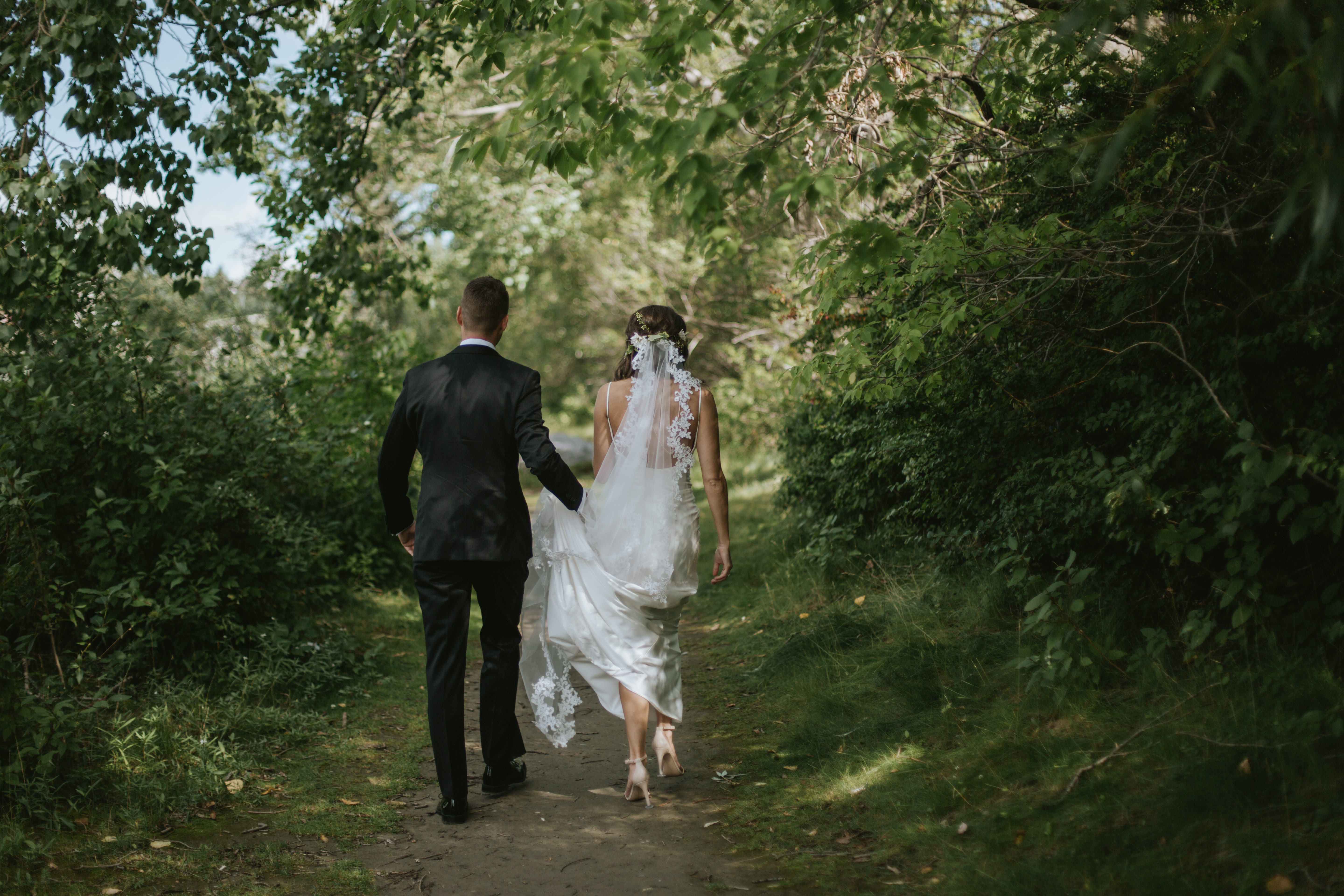 the bride and groom walk down a wooded path
