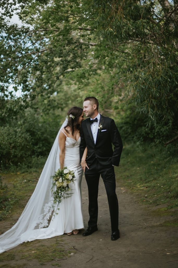 bride and groom stand on the path and laugh
