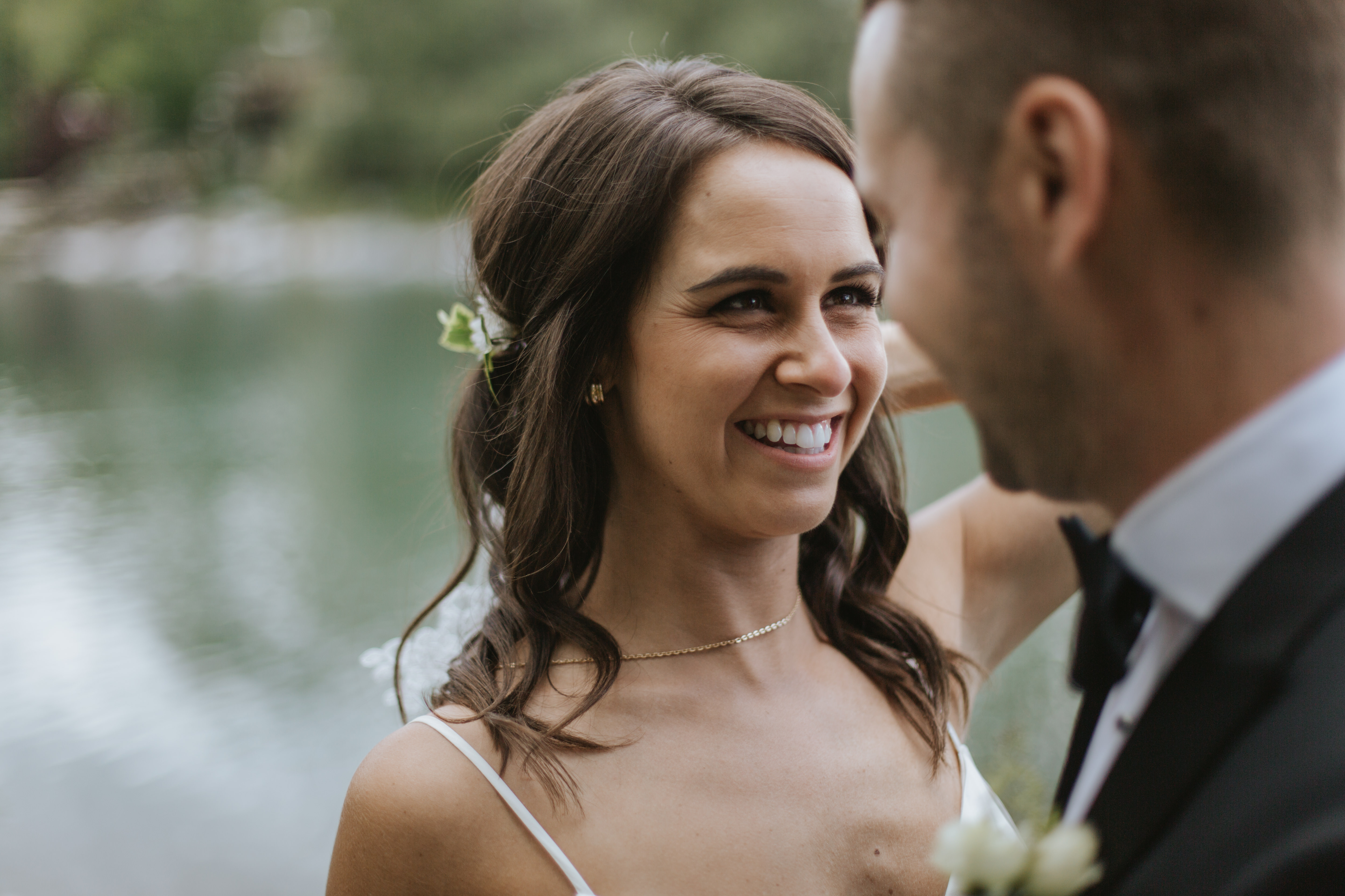 bride smiles at the groom and you can see her delicate necklace