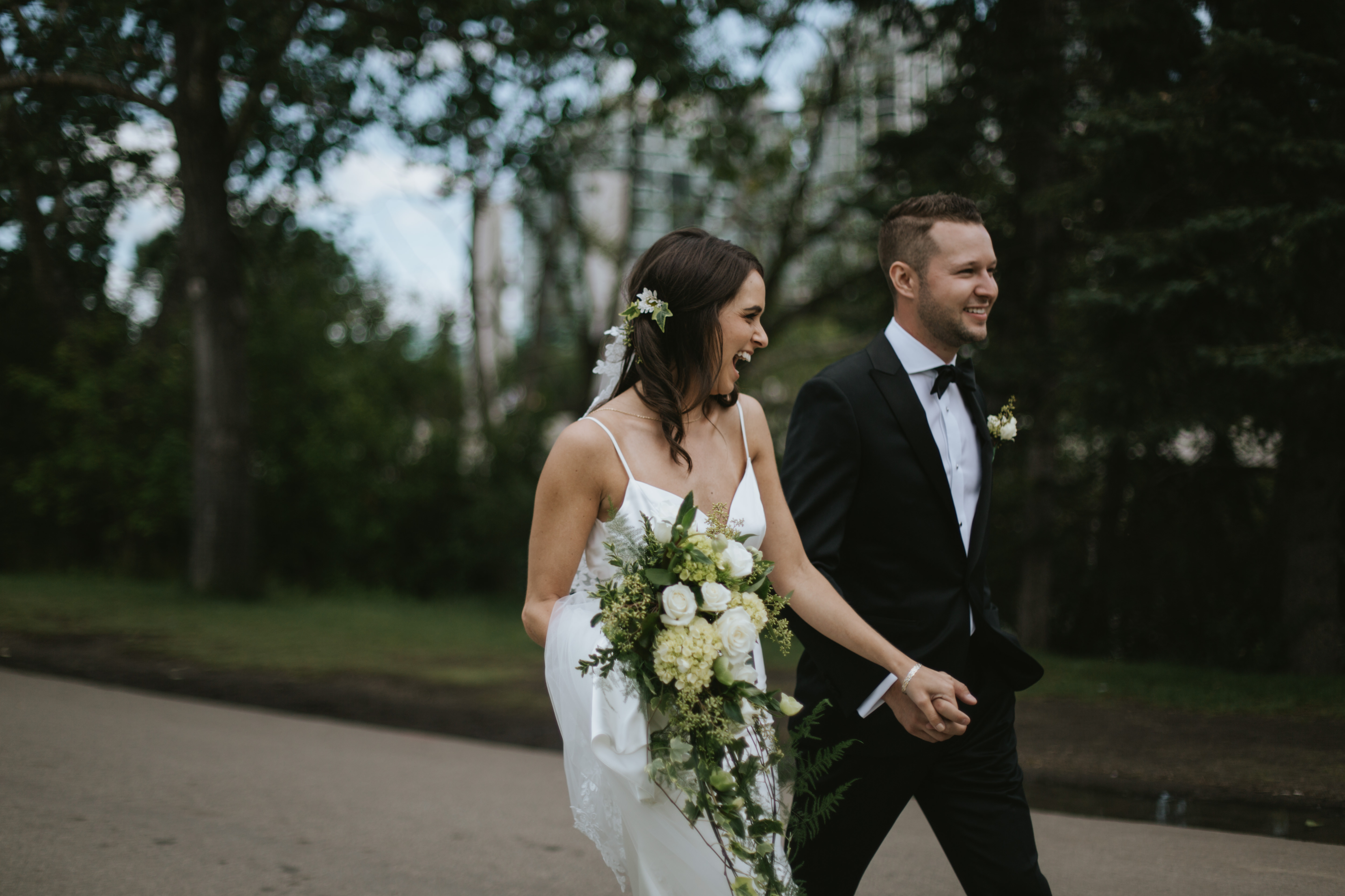 the bride and groom walk and laugh on a path