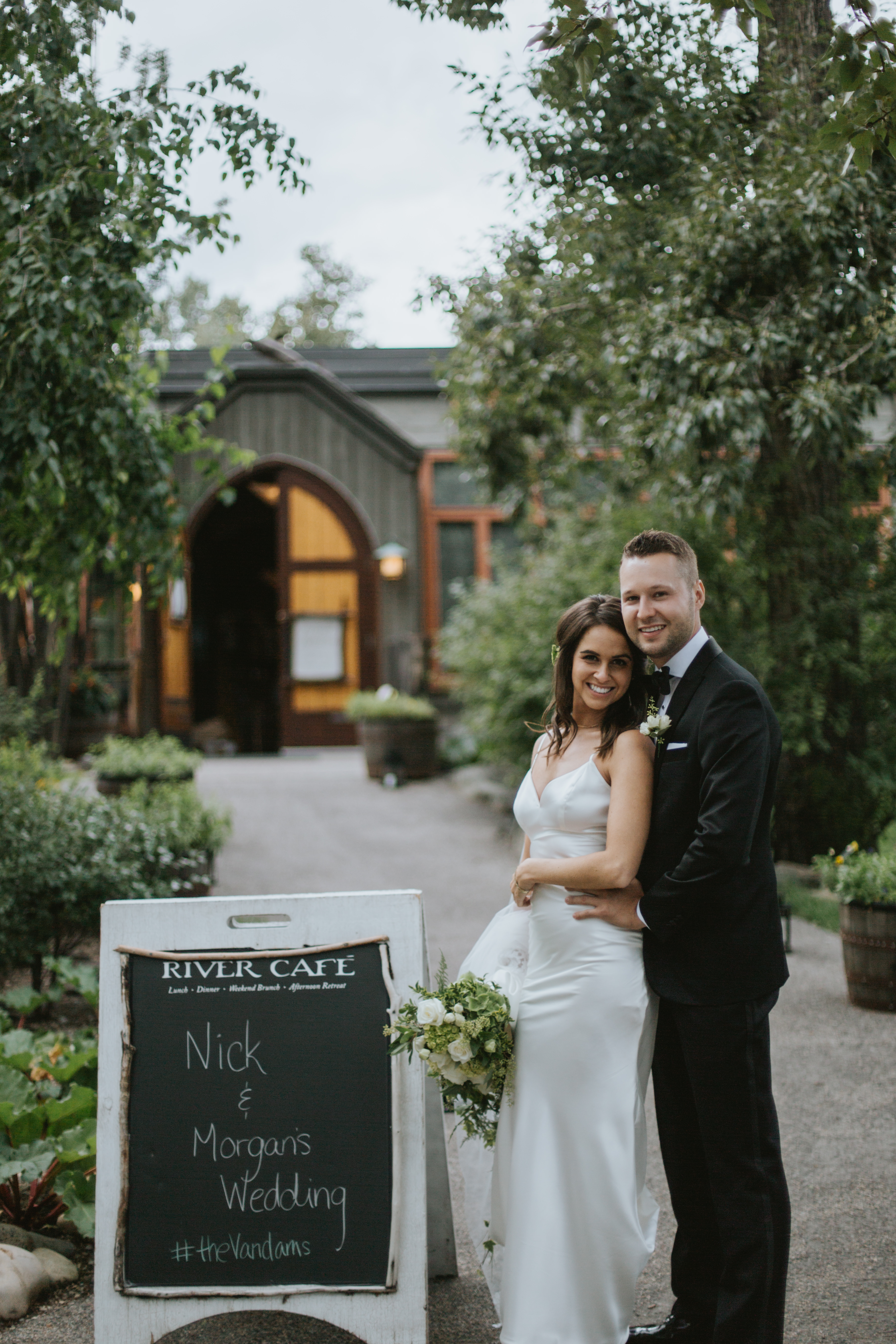 the bride and groom stand in front of the river cafe restaurant