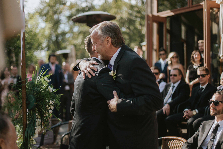groom and father of the bride hug