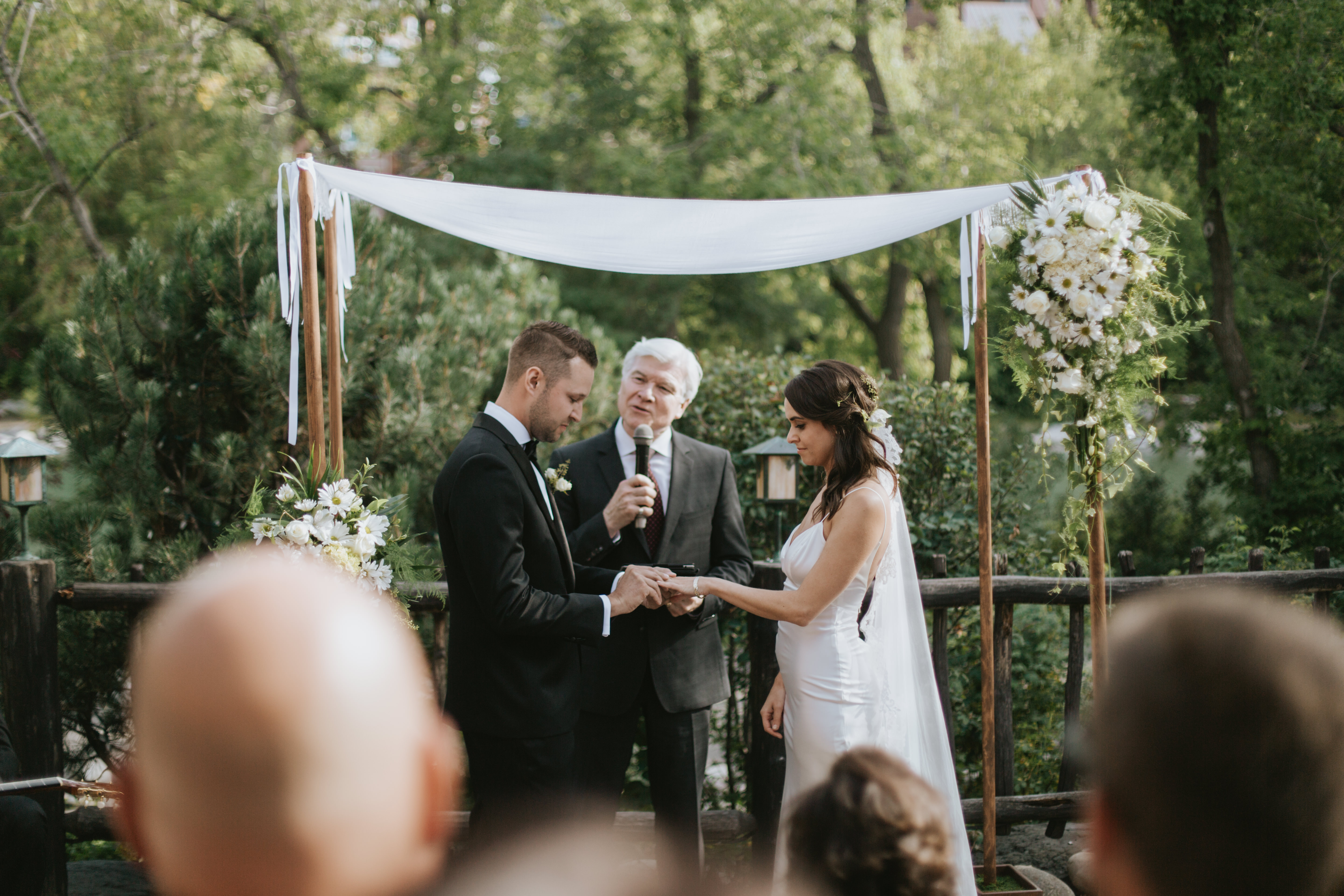 the groom places a ring on the bride's left hand