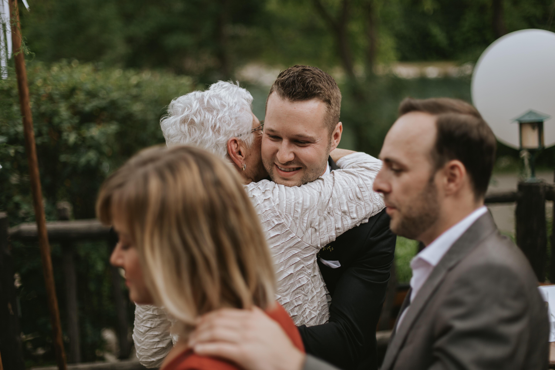 grandma hugs the groom in celebration