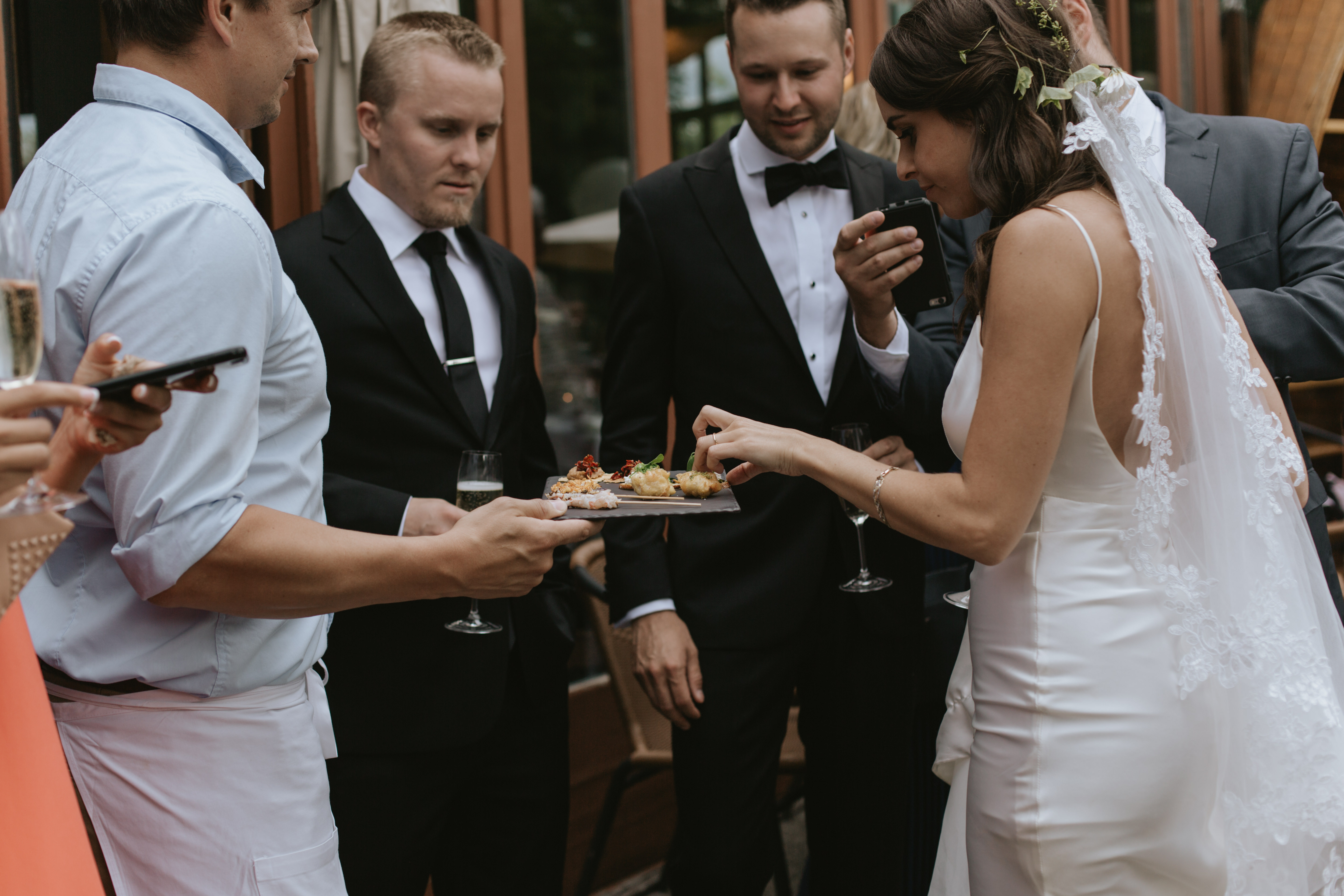 the wedding party eat hors d'oeuvres on the patio