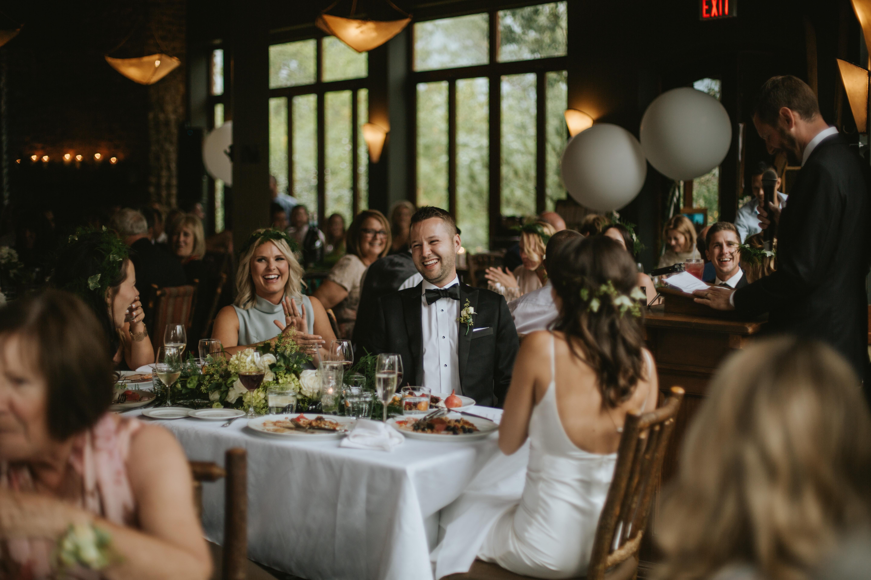 the groom laughs at a wedding speech
