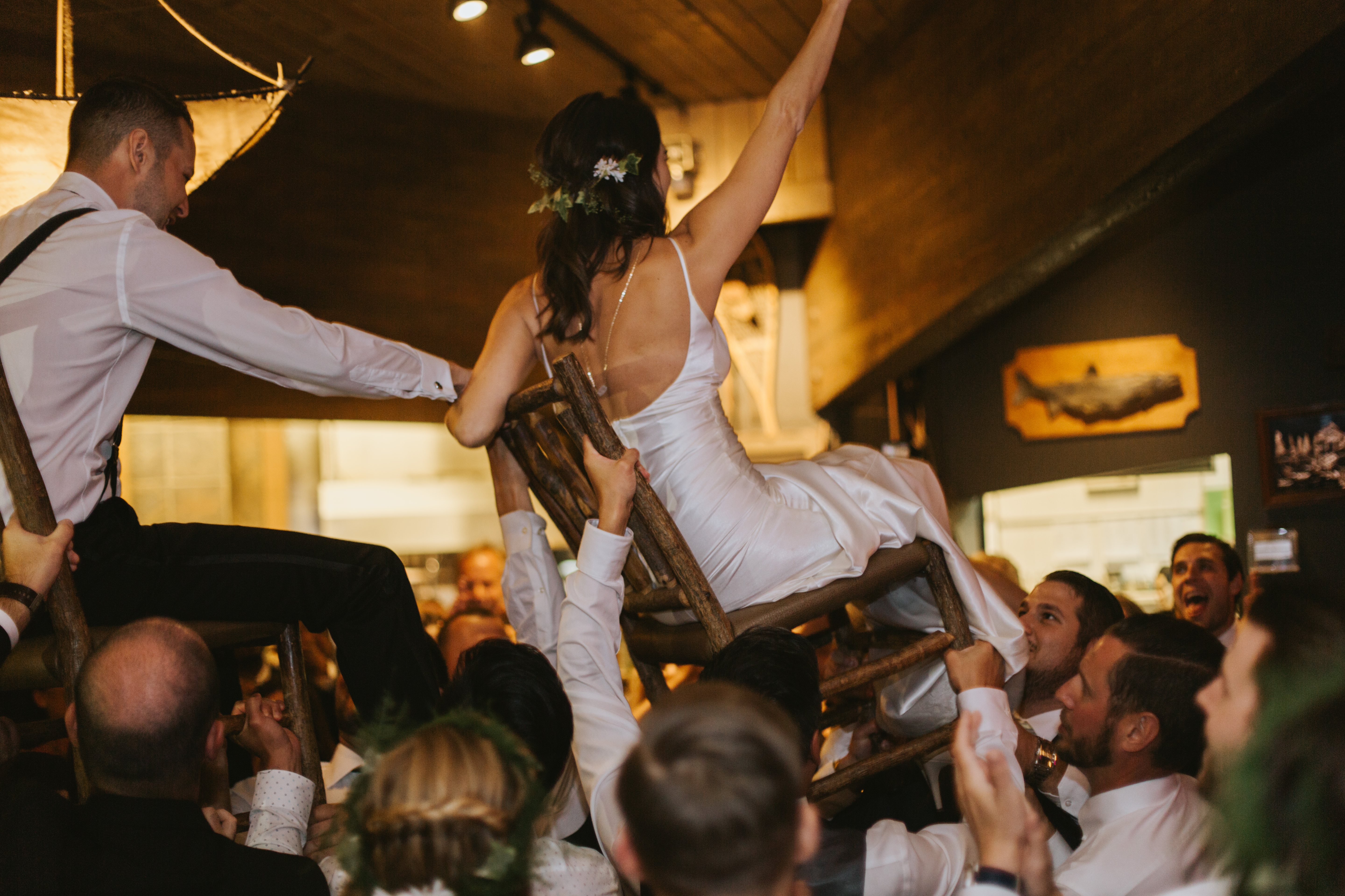 bride and groom are lifted up on chairs during the hora