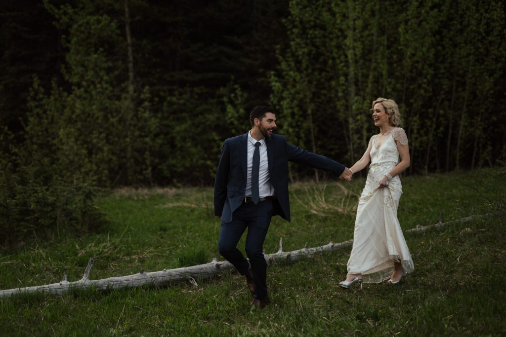 couple walk along the lake louise forest