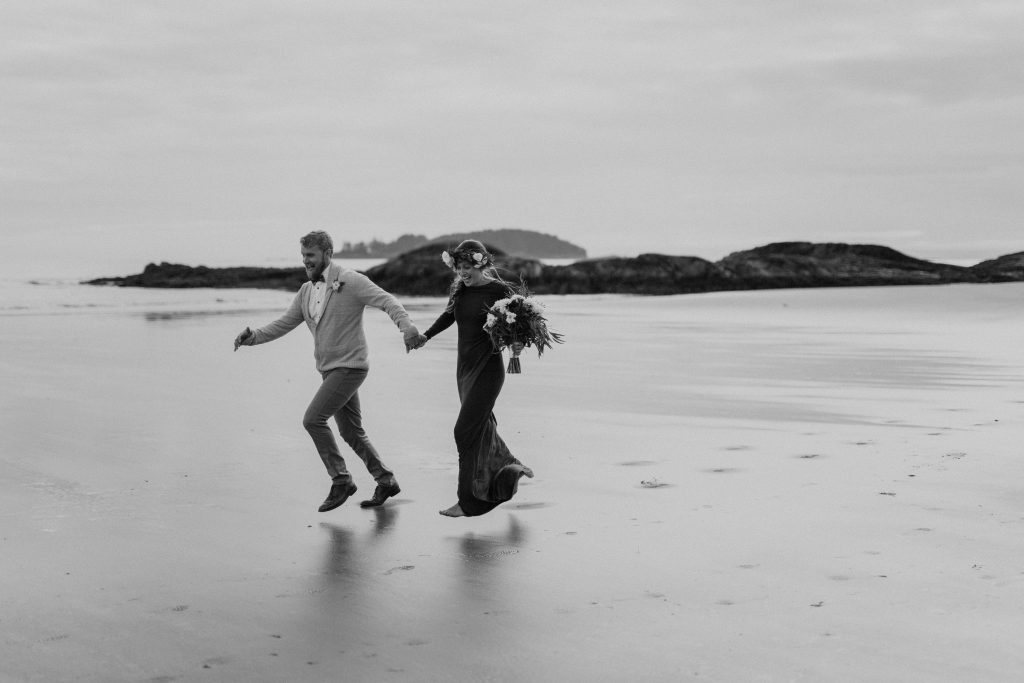 bride and groom run along the beach in tofino